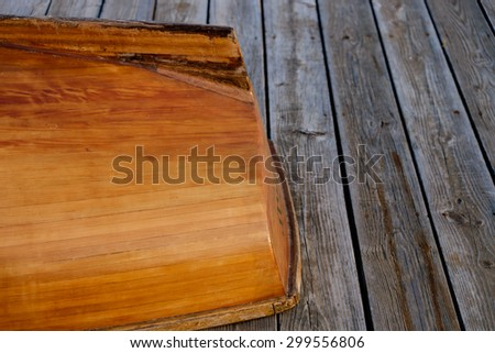 Hand crafted wooden rowboat stern laying on a deck upside down at dusk - stock photo