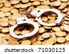Hand cuffs and coins as security concept - stock photo