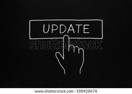 Hand cursor clicking Update button drawn with white chalk on blackboard. - stock photo
