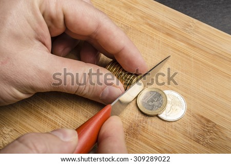hand cut euro coins with a knife on a cutting board, separating them as pieces of food - stock photo
