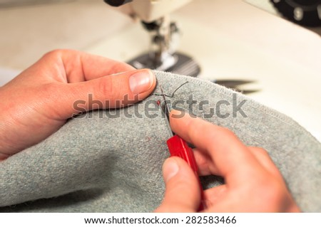 Hand cut open a seam on the fabric knife for ripping seams - stock photo