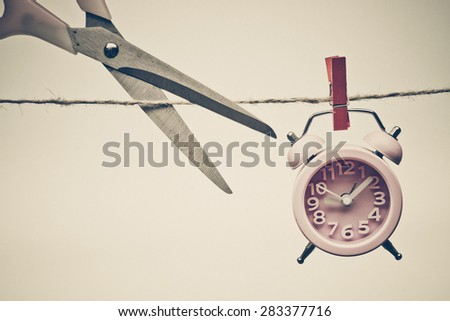 hand cutting a rope with a clock hung on by a wooden clip - importance of time - stock photo
