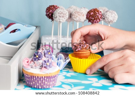 hand decorating cupcakes and cakepops - stock photo