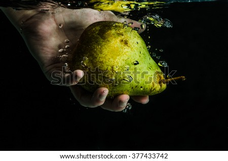 Hand dipping pear under water - stock photo