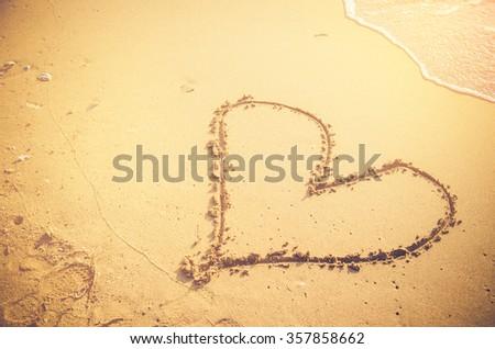 hand draw heart on sand beach valentine concept - stock photo
