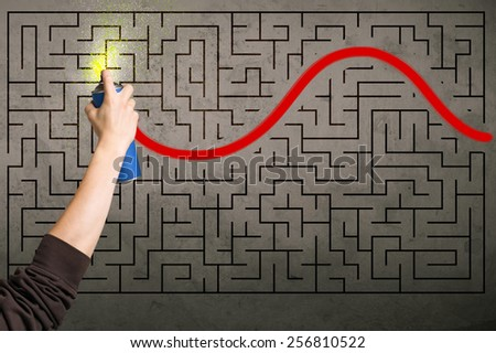Hand drawing a red solution line on the wall maze