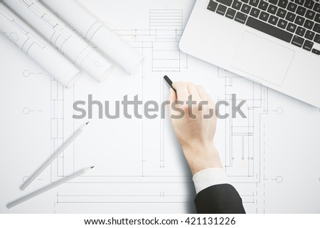 Hand drawing architectural project on large whatman with pencils and laptop computer on top. Architectural concept. Business man hand drawing construction sketch - stock photo