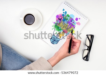 Hand drawing creative sketch in spiral notepad placed on white surface with coffee cup and glasses. Business idea concept