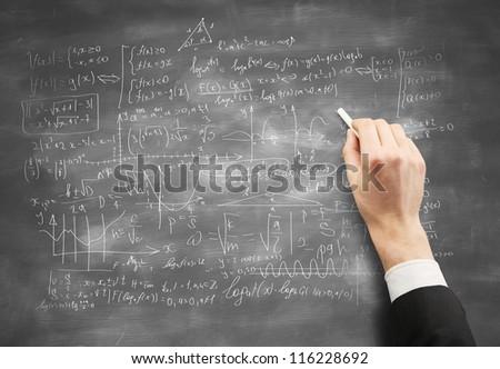 hand drawing formulas on  desk - stock photo