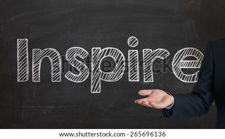 Hand drawing Inspire word presenting on blackboard by hand - stock photo