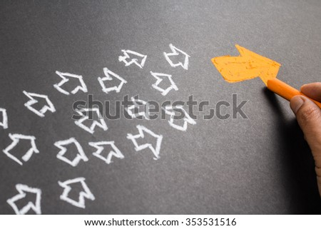 Hand drawing orange arrow as trend leader with many white arrows as follower - stock photo