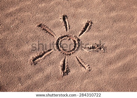 Hand drawn beautiful sun symbol on the sand at the beach. Lovely happy expression on sandy beach floor. Happy sunny hand drawn sun icon background. - stock photo
