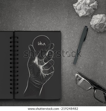 Hand drawn light bulb with IDEA word on dark note book as concept  - stock photo