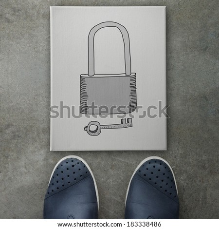 hand drawn of padlock and key on canvas board on front of business man feet as  Security concept  - stock photo