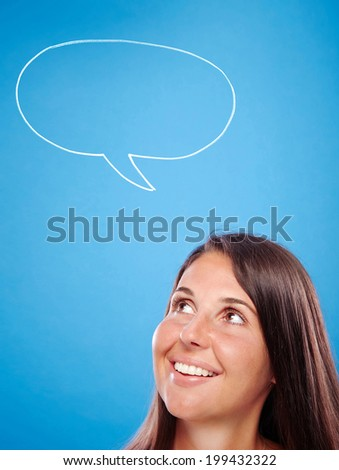 Hand drawn speech bubble on a blue background, young female looking at it.