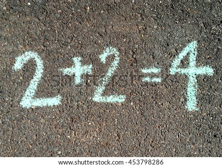 Hand Drawn Two Plus Two Equals Four Written in Blue Chalk on Concrete