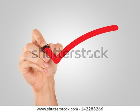 Hand draws red tick, approval sign. - stock photo