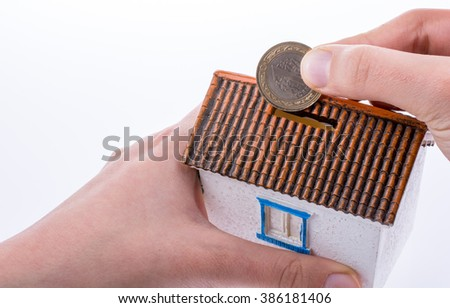 Hand dropping coin into the moneybox in the shape of a model house - stock photo