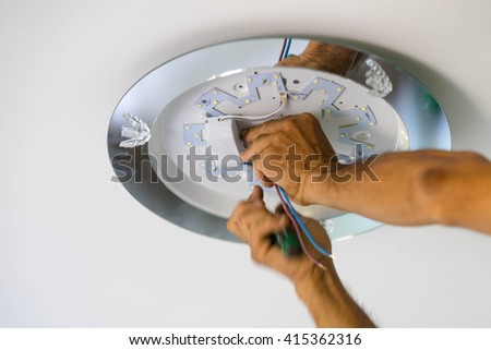 Hand Electrician Fixing Light On Ceiling - stock photo