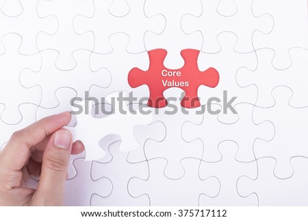 Hand embed missing a piece of puzzle into place, red space with word CORE VALUE concept.