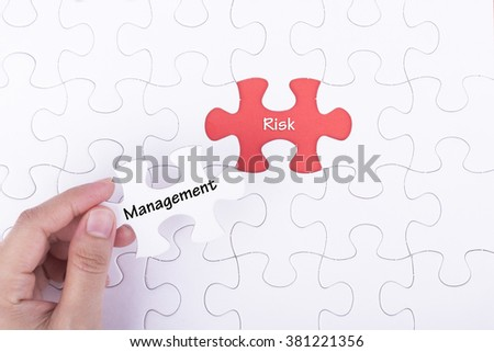 Hand embed missing a piece of puzzle into place, red space with word MANAGEMENT RISK. Business and financial concept.