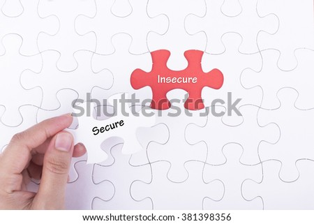 Hand embed missing a piece of puzzle into place, red space with word SECURE INSURANCE. Business and financial concept.