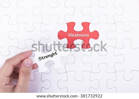 Hand embed missing a piece of puzzle into place, red space with word STRENGTH WEAKNESS . Business and financial concept.