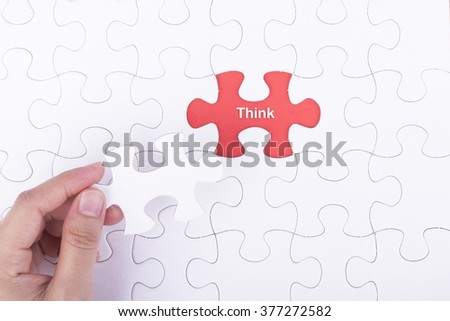 Hand embed missing a piece of puzzle into place, red space with word THINK concept