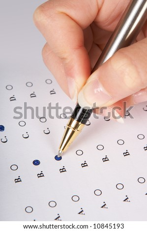 Hand filling in a multiple choice questionnaire - stock photo