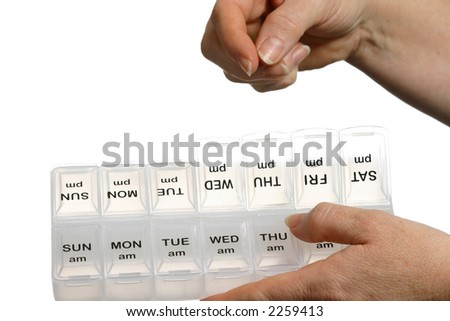 Hand filling pill dispenser with room to insert specific pill - stock photo