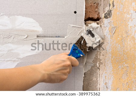 hand filling wall with spatula - stock photo