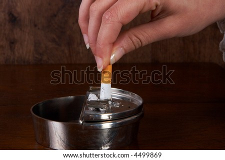 Hand finishing a cigarette in an ashtray - stock photo