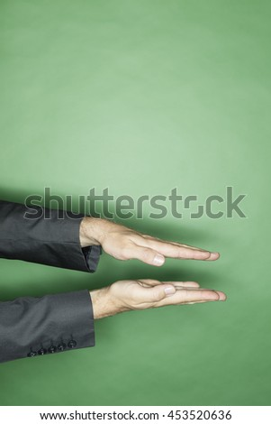 hand gesture of a male caucasian in a business suit: two flat hands showing a small distance or amount - stock photo