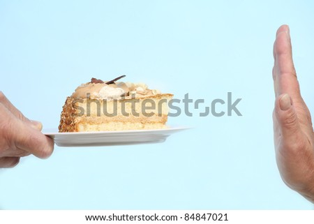 Hand gesturing no to a slice of cake - stock photo