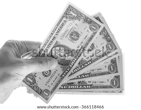 Hand giving dollar banknotes  currency of the United States  isolated over white in black and white
