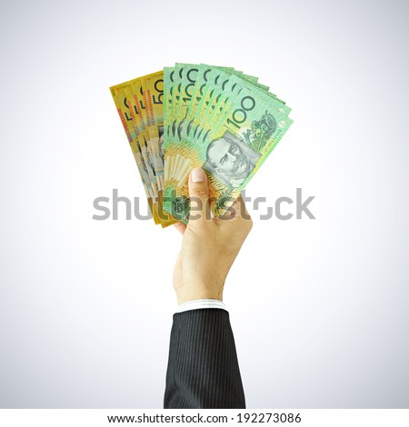Hand giving money - AUD - Australian Dollars - stock photo