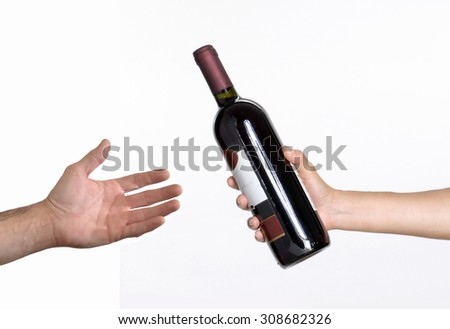 Hand giving red wine bottle. - stock photo