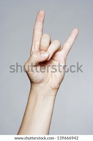 Hand giving the devil horns gesture - stock photo