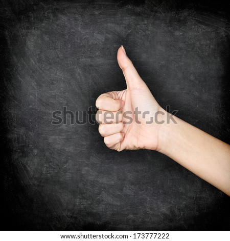 hand giving thumbs up on blackboard. Close up of thumbs up hand sign gesture of approval on chalkboard texture background. - stock photo