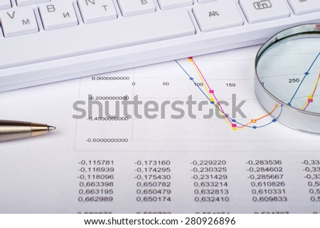 Hand glass with handle on document with numbers and keyboard