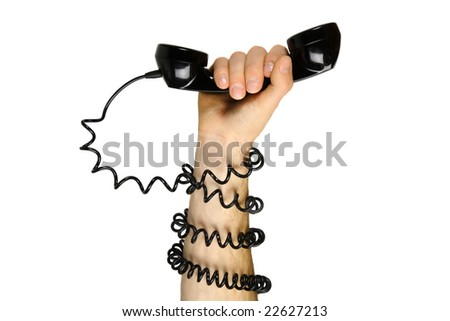Hand gripping telephone with cord wrapped around his arm. - stock photo