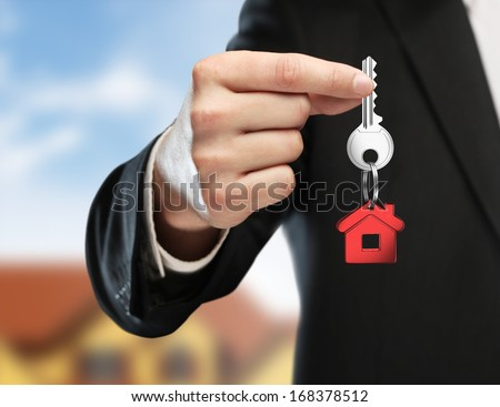 hand handing key on cottage background - stock photo