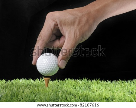 hand hanging golf ball on tee