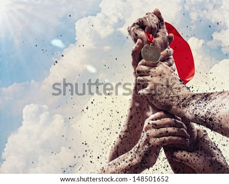 Hand held medal against the clear blue sky - stock photo