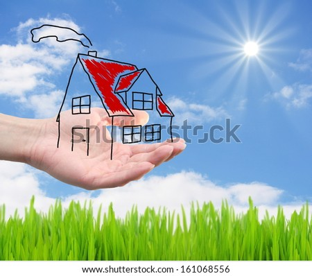 hand hold a house on a landscape - stock photo