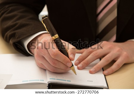 Hand hold a pen writing on the notebook. - stock photo