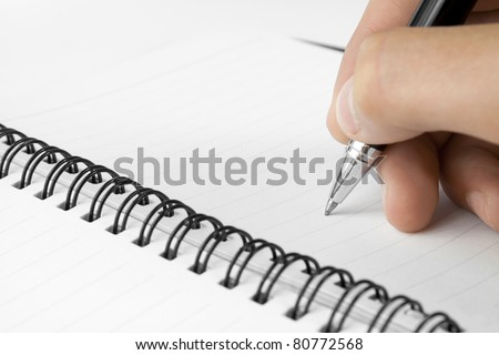 Hand hold a pen writing on the notebook - stock photo