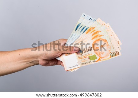 Hand hold a singapore currency, isolated on white background, a copy space, Count a money