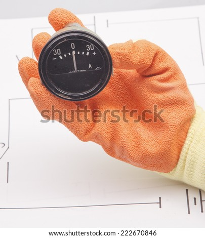 Hand hold ammeter on a background of the electric scheme