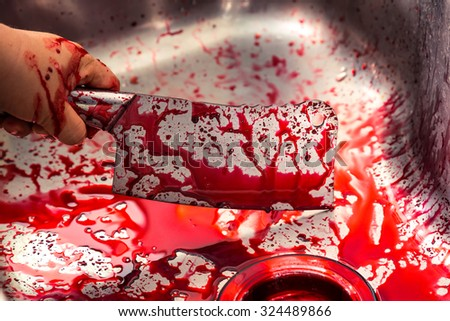Hand hold bloody knife in a steel shell for halloween - stock photo